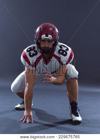 American football player getting ready before starting the game while standing against gray background