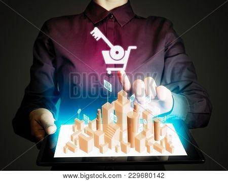 Woman Holds A Tablet Pc In Her Hands. Tablet Pc Has A Hologram With Real Estate For Sale. Concept Of
