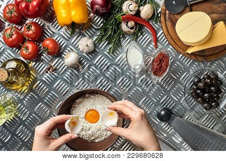 Set Of Ingredients For Pizza And Baker's Hand Smash Eggs Into Bowl On Metal Table