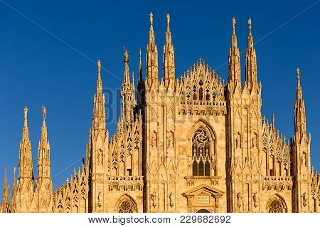Sunlit Facade Of Milan Iconic Gothic Cathedral Or Duomo Di Milano At Dusk, Front View, Milan, Italy