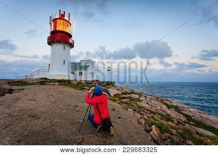 Female Tourist Traveler Taking Photo At Historic Red White Lighthouse On The Edge Of Rocky Sea Coast