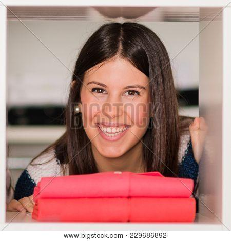 portrait of Happy Young woman through shelf
