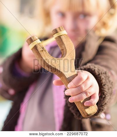 Blonde Girl Aiming With A Sling Shot, Outdoors