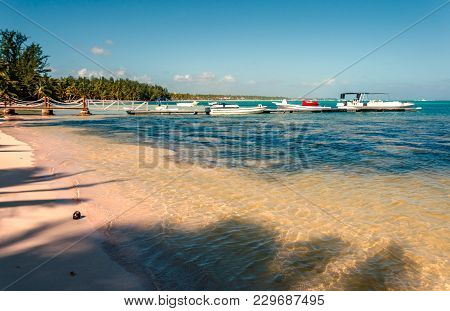 A Tropical Beach With Clear Ocean Water, Coconut On The Perch, A Jetty With Boats And Yachts, Palm G