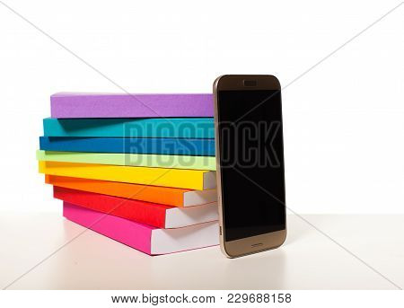 Modern Touchscreen Smartphone Near Pile Of Color Hardcover Books Isolated On White Background. Conce