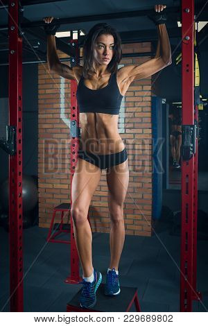 Fit Girl With Black Hair Wearing Black Short Top, Shorts And Gloves Standing With Horizontal Bar On