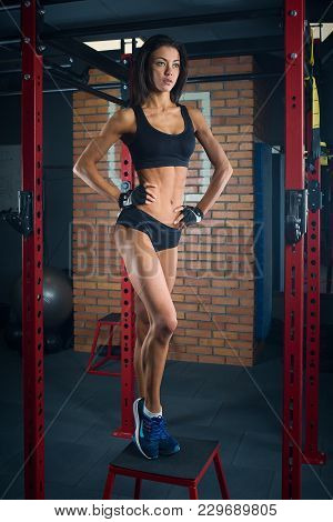Fit Girl With Black Hair Wearing Black Short Top, Shorts And Gloves Standing On Box In Gym, Brick Wa