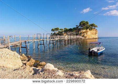 Wooden Bridge From Agios Sostis Leading To Small Rocky Island. Bay Of Laganas, Zakynthos Island, Gre