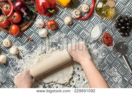 Female Hands Roll Out Dough On Metal Background, Close Up. Chef Makes Dough. Table With Vegetables A
