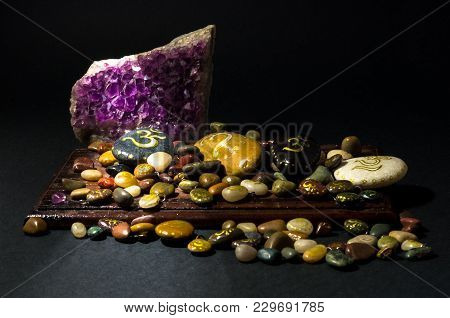 Amethyst Crystal And Colorful Stones Over A Wooden Board