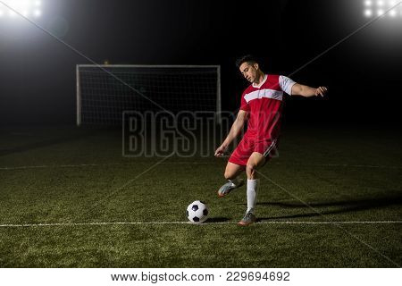 Fit Young Football Player Kicking The Soccer Ball On Green Pitch During Competition Match