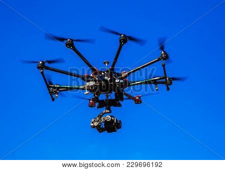 Quadrocopter With A Camera Flying In A Blue Sky Controlled By A Wireless Remote Control, Digital Hum