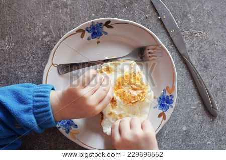 Kid Hands And Fried Egg, Fork And Knife On White Flower Patterned Plate On Grey Grunge Table Backgro