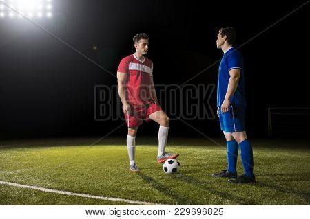 Two Rival Football Player Standing On Field With Ball And Looking At Each Other