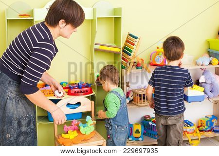 The Mom Tidy Up The Toys And Teaches The Little Child Clean Up In The Playroom