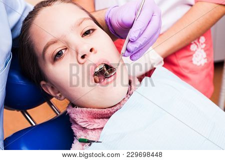 A Girl Tries To Establish A Retainer For Teeth Dental Braces , Sitting In A Dental Chair