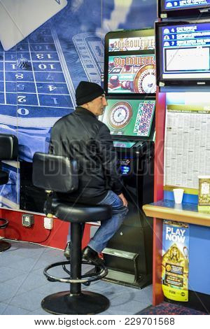 London, Uk - Mar 5, 2018: Mature Man Using Fixed Odds Roulette Machine In Bookmakers. London, Englan
