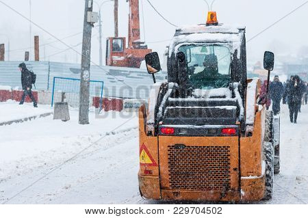 Yellow Snowplow Removing Snow During Heavy Snowfall. Winter Street Maintenance In Hard Weather Condi