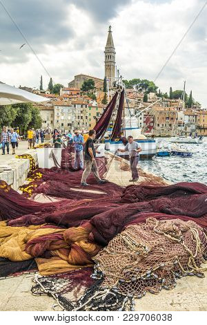 Rovinij, Croatia, September 27, 2017: Fisher In On The Dock Are Repairing Their Fishing Net In The M