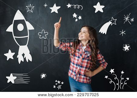 Exploring Space. Cheerful Emotional Little Girl Pointing To The Sky And Feeling Excited While Thinki