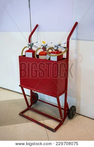 Old Two- Wheel Mobile Fire Cart Filled With Three Red Extinguishers At Fire Safety Point.