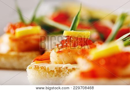 Bruschetta White Bread With Shrimp White Sauce And Red Caviar. Decorated With Lemon And Shallots. Un