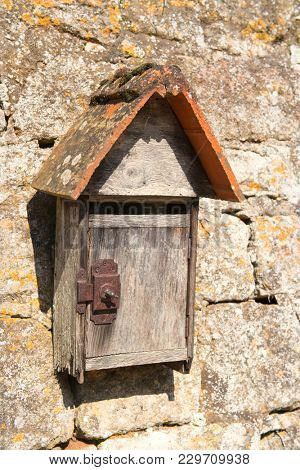 Old vintage letterbox hanging at the stone wall