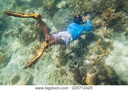 snorkeling diver make a free diving on tropical reef with blue background and reef fish in andaman sea indian ocean Thailand