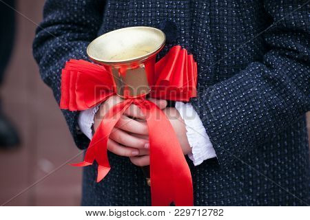 Close Up Shot Of Pupil Hands Holding School Bell With Red Ribbon. Back To School Concept. First Sept