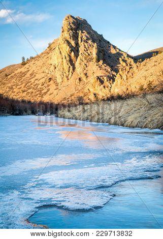 Eagle Nest Rock and partially frozen North Fork of Cache la Poudre River in northern Colorado at Livermore near Fort Collins, winter scenery