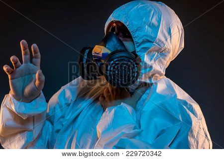 Pandemic, virus infection concept. Man in protective suit and antigas mask with glasses. Ebola, toxic gases, biological warfare, infections and diseases