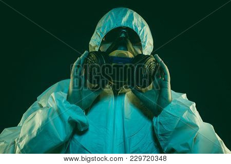 Hazmat Contagious virus infection concept. Man in protective suit and antigas mask with glasses. Ebola, toxic gases, biological warfare, infections and diseases