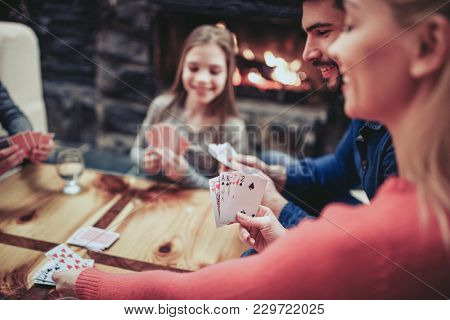 Young family playing card game at home