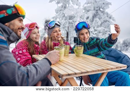 Happy family enjoying on tea and making selfie at ski resort