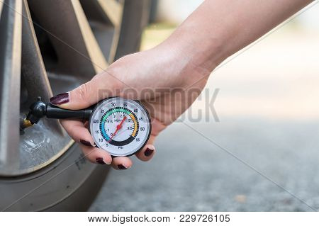 Female Hand Holding A Pressure Gauge For Measure Car Tyre Pressure