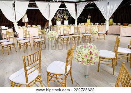 The Guest Chairs In Gold Color Theme With White Cover, The Beach Wedding Venue With The Ocean In Bac
