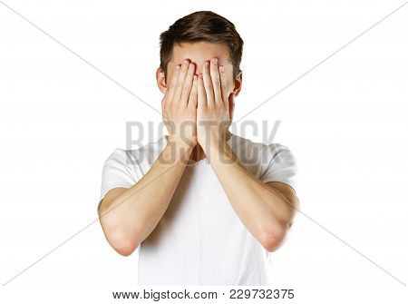 Man In White T-shirt Covering His Face With Hands Over White Background.