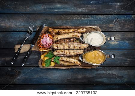 Grilled Sausages With Sauerkraut, Mustard And Potato Wedges. Served With Cutlery On The Wooden Backg