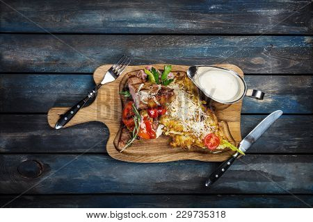 New York Steak With Potato Pancakes On The Rustic Board With Cutlery And Wooden Background, Top View