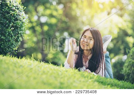 Relaxed Young Beautiful Woman With Smiling Face Enjoy Eating Pork Stick In The Park. Time To Relax A