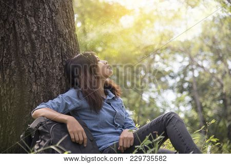 Happy Woman Enjoy And Relax With The Nature. Young Beautiful Woman Sitting Under The Big Tree In Gre