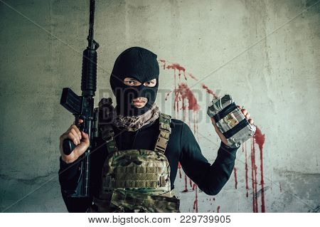 A Terrorist Wearing A Hat To Hide His Face, He Is Holding A Gun And Bomb.