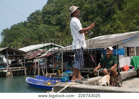 KOH CHANG, THAILAND - FEB 17, 2018: Locals of Fishing village on the Eastern shore, which consists of houses on stilts built into the sea. Island consisting of 8 villages with 5,356 inhabitants.