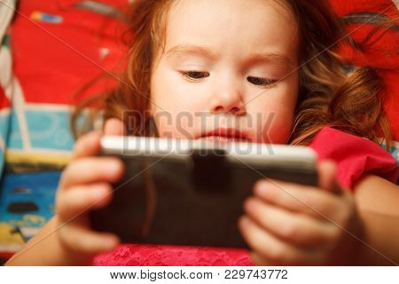 The Girl Looks At The Phone Closely. The Dangers Of Gadgets For Children's Vision.