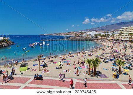TENERIFE ISLAND, SPAIN - APRIL 10, 2017 : Tourists are sunbathing on Colon beach on the Costa Adeje on Tenerife. Canary Islands. Spain