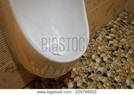 Mothballs in the white men urinal in a toilet to avoid the disturbing insects