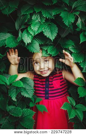 Cute Girl With A Smile Peeking Out From Under The Green Leaves. Beautiful Baby In Red Summer Dress.