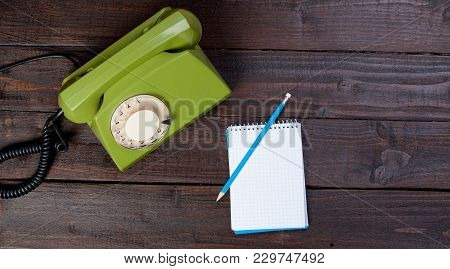 Green Dial Phone And Note With Pencil On Wooden Background