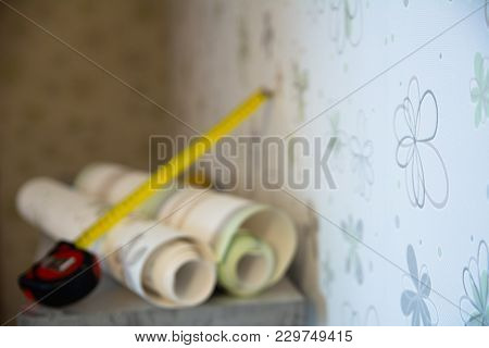 Two Rolls Of Wallpaper And A Measuring Tape