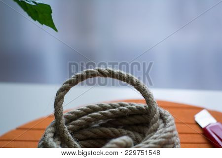 Coarse Rope Roll And A Knife With Red Handle Against